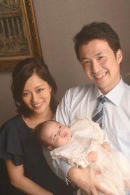 笑顔のご両親とお父様に抱かれた赤ちゃん