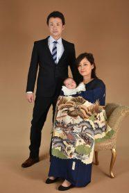 掛け着を着たお母様とスーツのお父様と産着を着た赤ちゃん