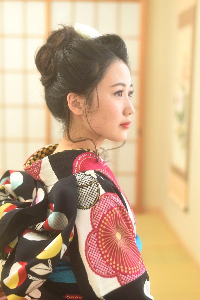 大きい花柄が描かれた白×黒の振袖を着た女の子の横顔姿。