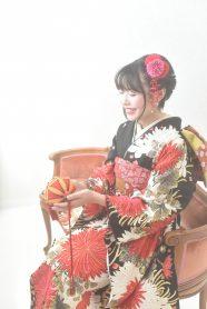 白と赤の花が描かれた黒色の振袖を着て、鞠を持った女の子