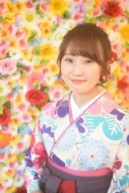 花の背景に、花柄の白い着物とえんじ色の袴を着た女の子