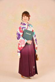 花柄の白い着物にえんじ色の袴を着た女の子